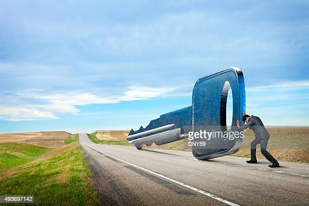 Businessman Is Pushing Key Down A Rural Road