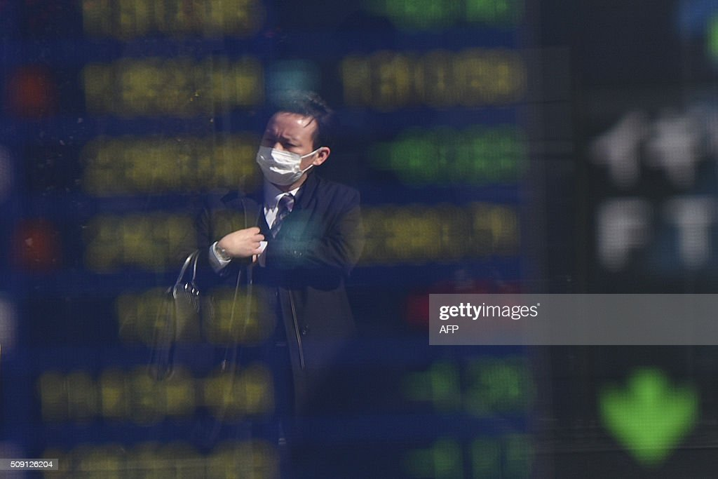 A businessman is reflected on an electric quotation board flashing share price indexes of the Tokyo Stock Exchange (TSE) in front of a securities company in Tokyo on February 9, 2016. Tokyo shares tumbled nearly five percent, extending a global sell-off as a stronger yen dented exporters and after oil prices tanked again on fears of a deepening economic slowdown. AFP PHOTO/Toru YAMANAKA / AFP / TORU YAMANAKA