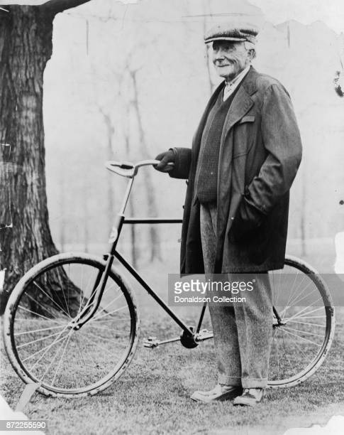 Businessman John D Rockefeller poses for a portrait with a bicycle in 1913