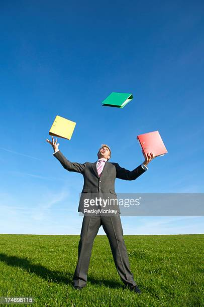 Businessman Juggling File Folders in Bright Meadow