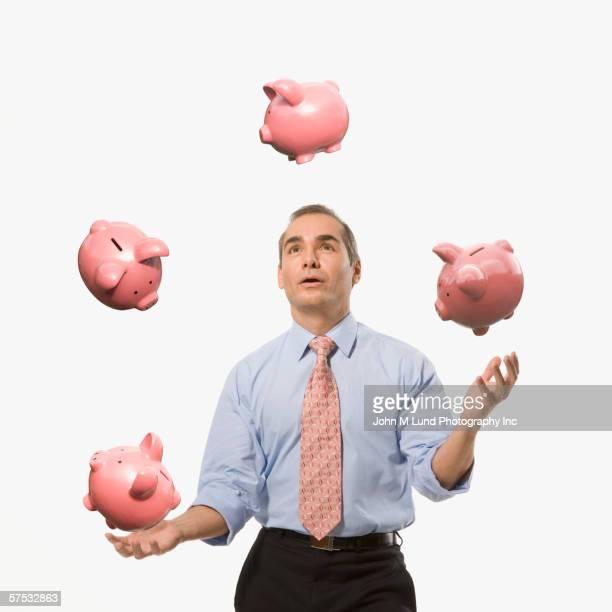 Businessman juggling piggy banks