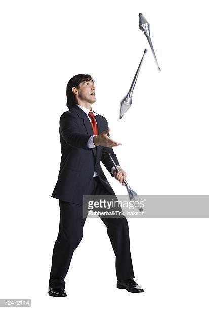 Businessman juggling pins
