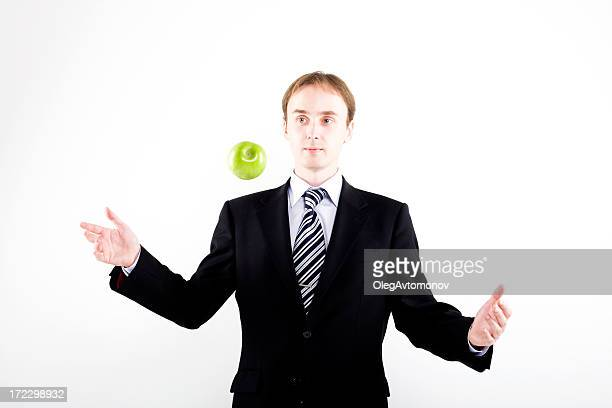 Businessman juggling with apple