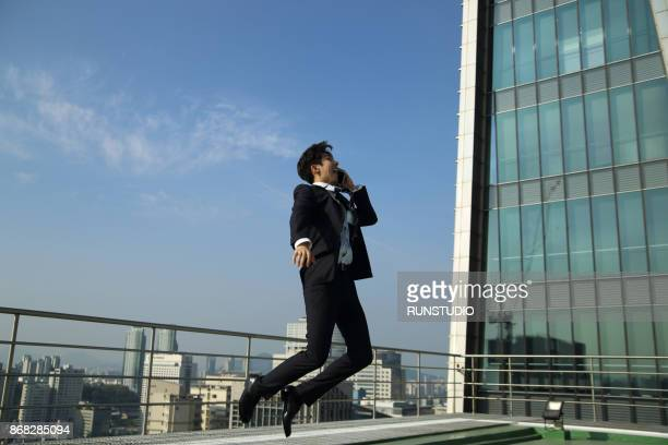 businessman jumping and talking on smart phone