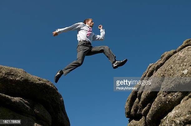 Businessman Jumping Between Rocks