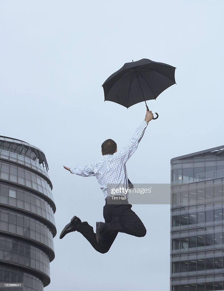 Businessman jumping for joy outdoors : Stock Photo