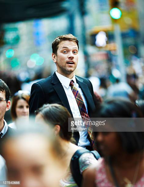 Businessman jumping in city crowd.