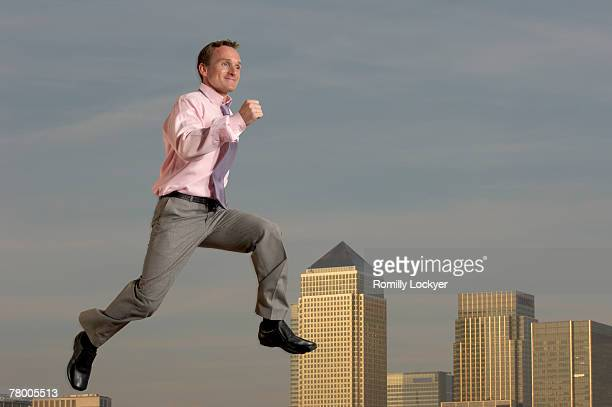 Businessman jumping in front of cityscape