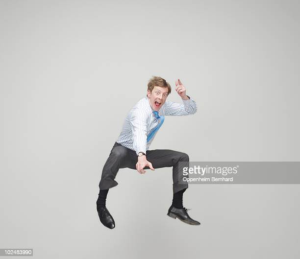 businessman jumping in the air smiling