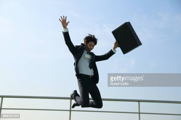 Businessman jumping in the air with briefcase