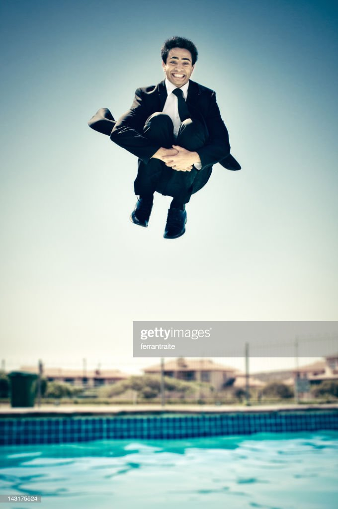 Businessman jumping in the pool : Stock Photo
