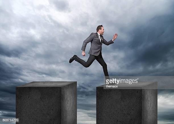Businessman jumping on concrete blocks