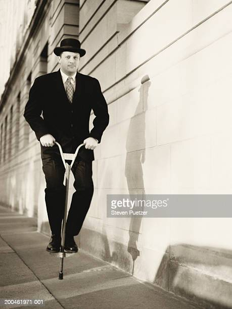 Businessman jumping on pogo stick on footpath, (digital enhancement)