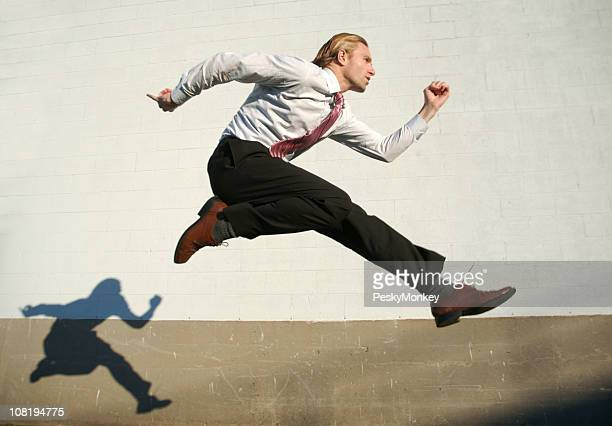 Businessman Jumping Outdoors Across White Wall with Shadow