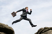 Businessman Jumping Outdoors Between Rock and Hard Place White Sky