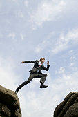 Businessman Jumping Outdoors Over Valley Between Rocks
