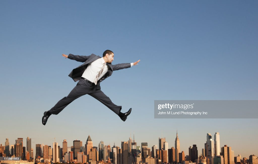 Businessman jumping over highrise buildings : Stock Photo