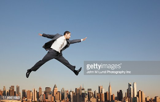 Businessman jumping over highrise buildings : Foto de stock