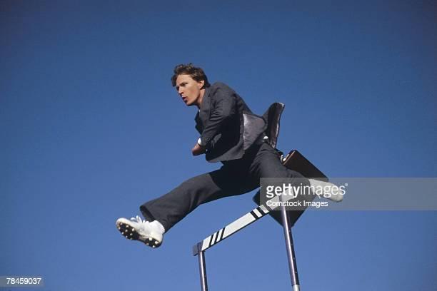 Businessman jumping over hurdle