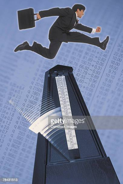 Businessman jumping over metronome