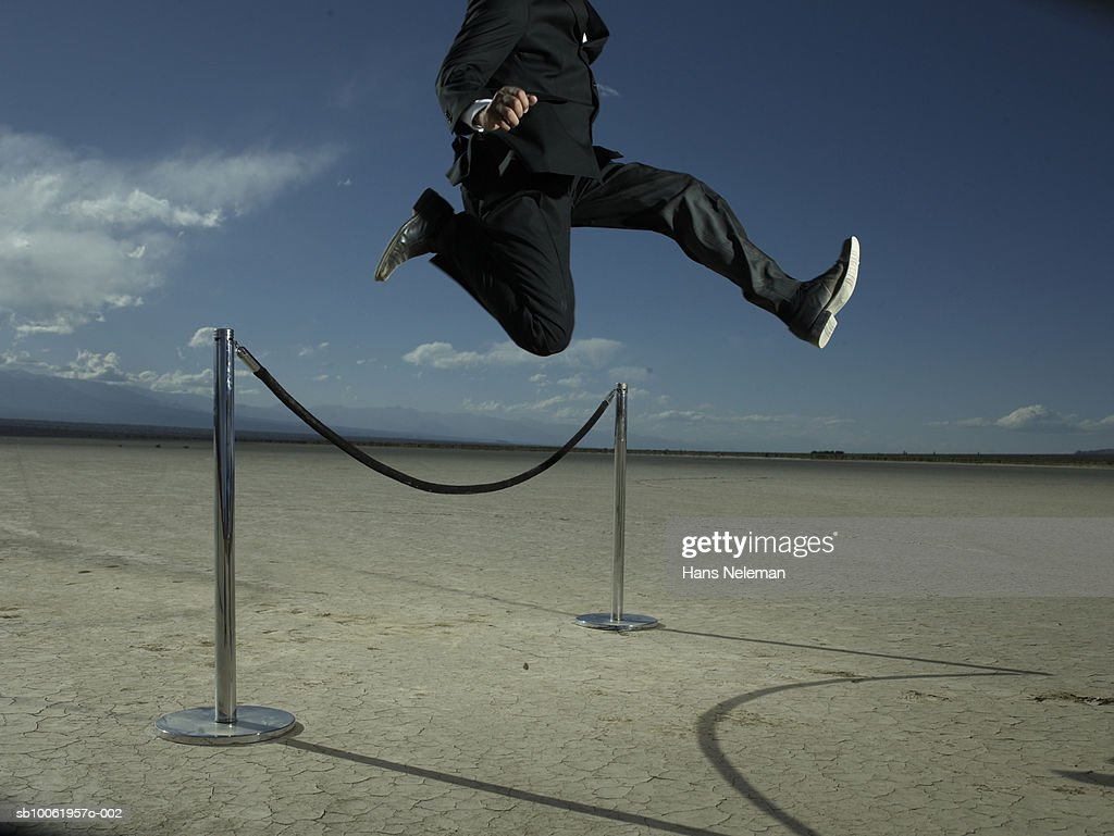 Businessman jumping over velvet rope barrier, low section : Stock Photo