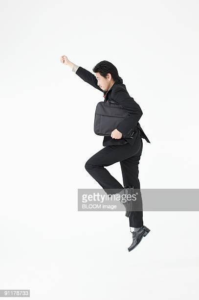 Businessman jumping, raising hands, side view, studio shot