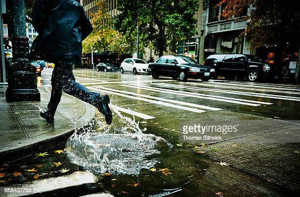 Businessman jumping through puddle on city street
