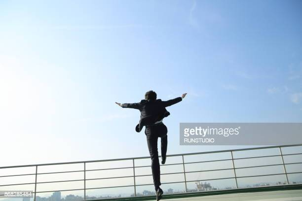 businessman jumping up on rooftop