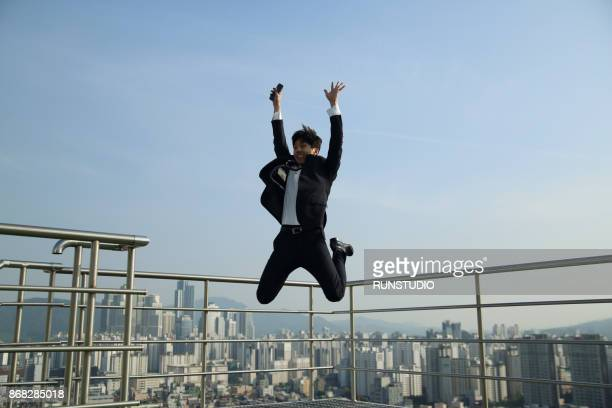 Businessman jumping with cell phone