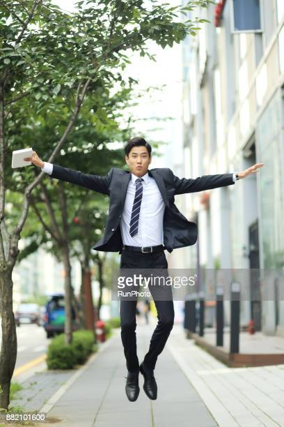 Businessman jumping with digital tablet