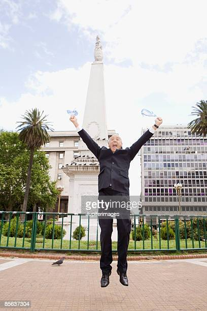 Businessman jumping with flags, Buenos Aires, Argentina