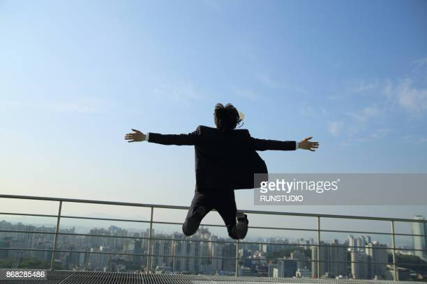 Businessman jumping with his arms outstretched
