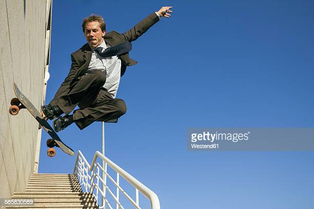Businessman jumping with his skateboard