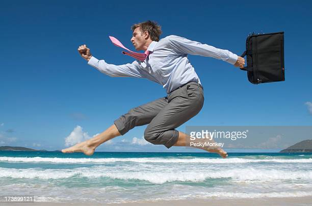 Businessman Jumping With Laptop Bag Over Tropical Beach