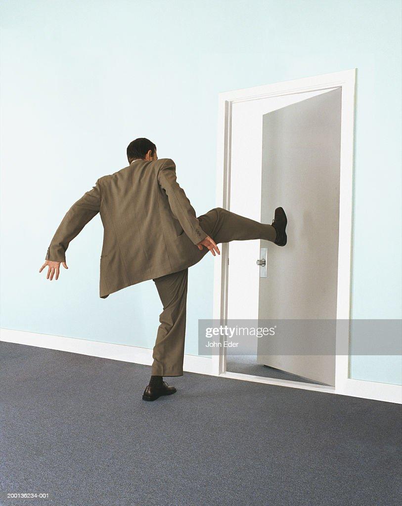 Kicked In Door : Businessman kicking door rear view stock photo getty images