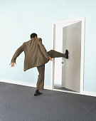 Businessman kicking door, rear view
