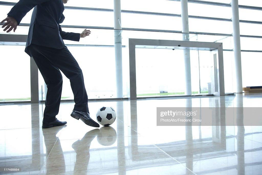Businessman kicking soccer ball in lobby