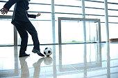 Businessman kicking soccer ball in lobby