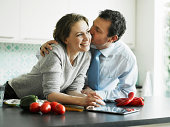 Businessman kissing wife in kitchen