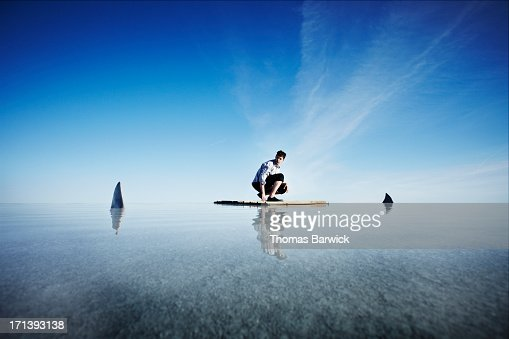 Businessman kneeling on life raft watching sharks : Stock Photo