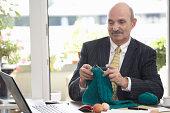 Businessman knitting at desk