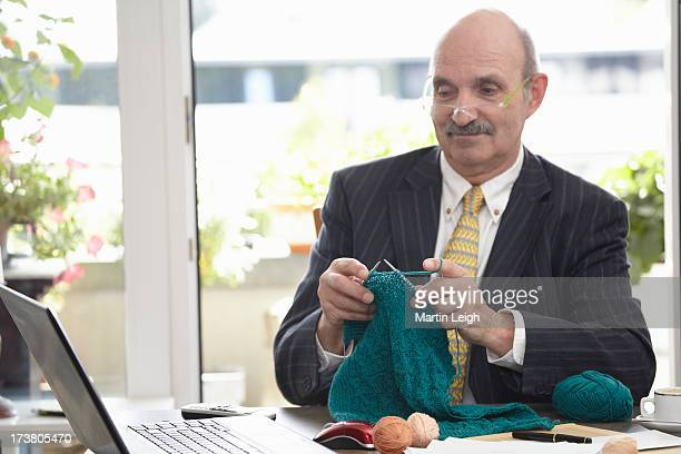 Businessman knitting at desk