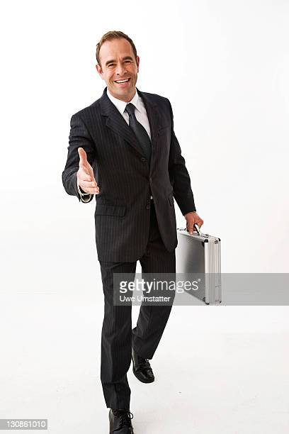 Businessman laughing, hand stretched out to shake hands