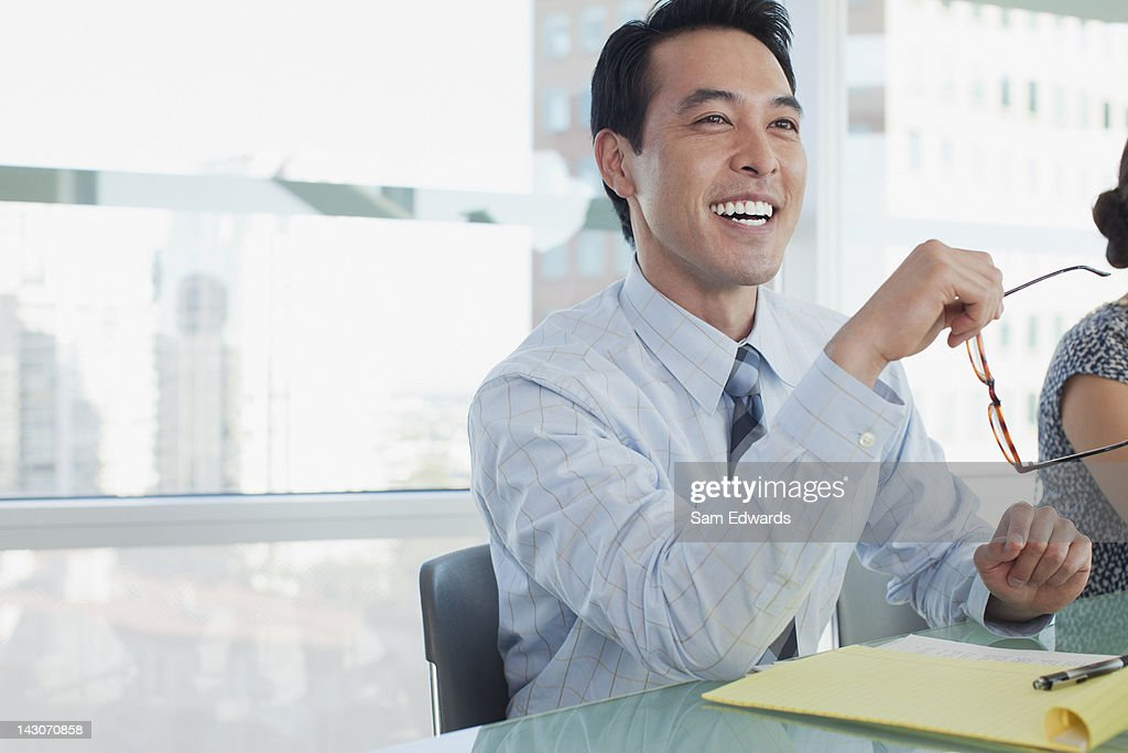 Businessman laughing in meeting : Stock Photo