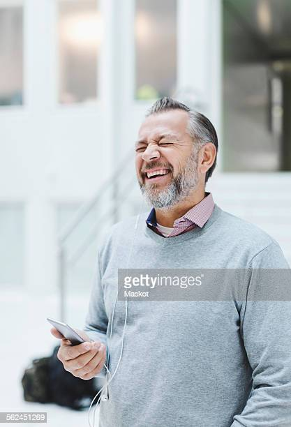 Businessman laughing while communicating through headphones in office