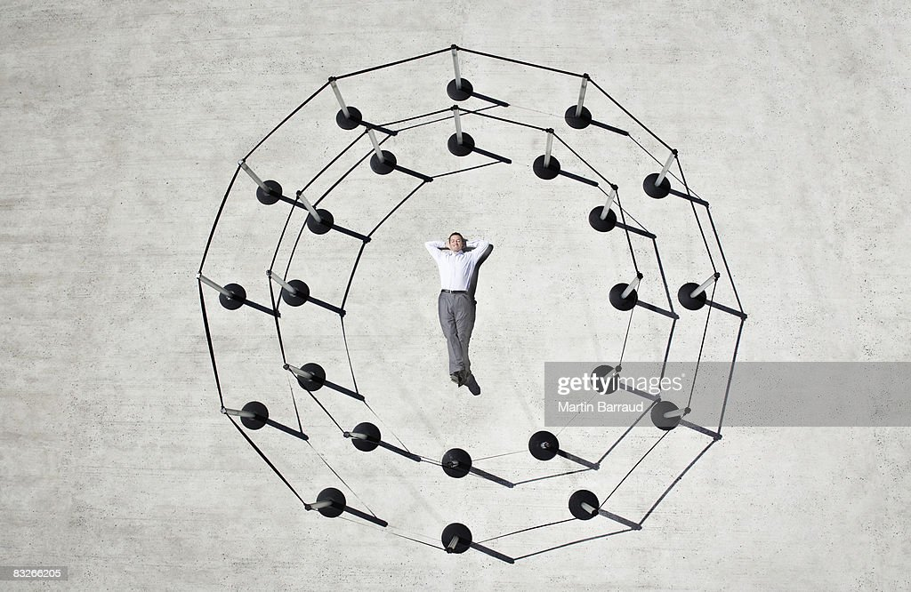 Businessman laying in circle of cordon posts : Stock Photo