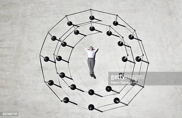 Businessman laying in circle of cordon posts