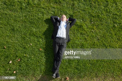 Businessman laying in grass