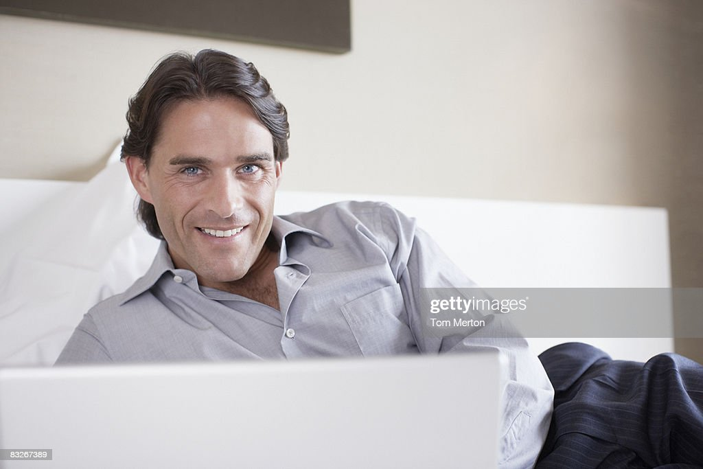 Businessman laying on bed in hotel room : Stock Photo