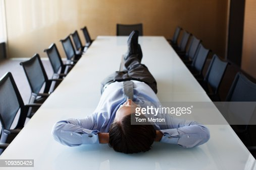 Businessman laying on conference room table : Foto de stock